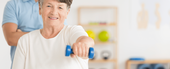 Older adult woman lifting a hand weight in physical therapy.